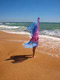 Girl with pareo standing on a sunny beach Stock Photo