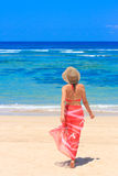 Girl in pareo walking towards. Young female in pareo walking towards the sea Stock Photo