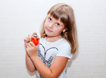 Girl with parfume. Teen girl poses with red parfume bottle in her hands Royalty Free Stock Photography