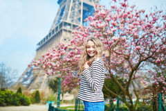 Girl in Paris near the Eiffel tower and pink magnolia Stock Images