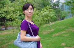 Girl in a park. Beautiful girl in a park with a hand bag Royalty Free Stock Photo