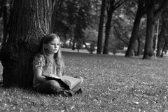 Girl in a park. A young girl reads a book in the park. Black and white photography royalty free stock photo