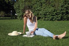 Girl in park. Young girl reading a book in the park royalty free stock photography