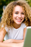Girl In Park. A young attractive woman using laptop in the park royalty free stock images