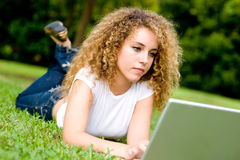 Girl In Park. A young woman lying on the grass with laptop computer royalty free stock image