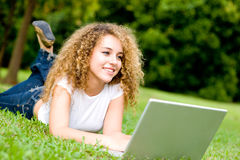 Girl In Park. A young woman lying on the grass with laptop computer stock photos