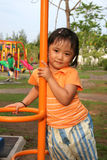 Girl at the park. Girl wearing orange tee playing at the park Stock Image