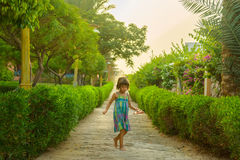 Girl  in  park alley. Girl goes barefoot in the park alley Royalty Free Stock Photo
