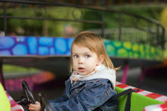 Girl at park amusement. Small beauty girl at park amusement - on small toy machine, drive stock images