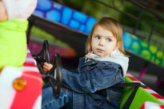 Girl at park amusement. Small beauty girl at park amusement - on small toy machine, drive royalty free stock photos