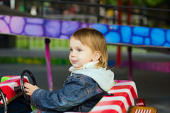 Girl at park amusement. Small beauty girl at park amusement - on small toy machine, drive stock image