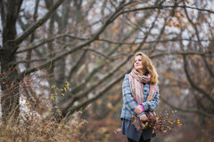 Girl in the Park. Beautiful girl in the autumn park. In a long scarf and a plaid coat Stock Photos