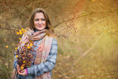 Girl in the Park. Beautiful girl in the autumn park. In a long scarf and a plaid coat Stock Photography