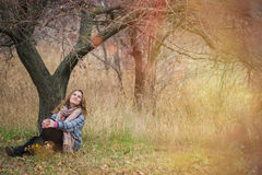 Girl in the Park. Beautiful girl in the autumn park. In a long scarf and a plaid coat Royalty Free Stock Photography