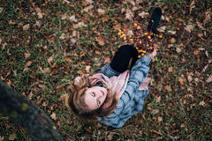Girl in the Park. Beautiful girl in the autumn park. In a long scarf and a plaid coat Royalty Free Stock Photos