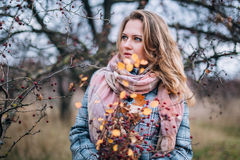 Girl in the Park. Beautiful girl in the autumn park. In a long scarf and a plaid coat Stock Photo