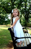 Girl on Park Bench. Happy little girl standing on a park bench Royalty Free Stock Photos
