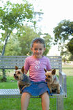Girl (4-6) on park bench with dogs, smiling, portrait Royalty Free Stock Photo