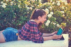 Girl on park bench playing with tablet stock photography