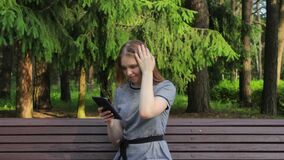 A girl in a Park on a bench, reading messages on a tablet and emotionally