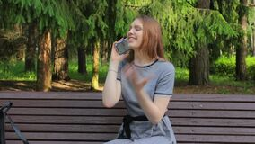 A girl in a Park on a bench, talking on a smartphone, emotionally behaves, gestures, argues and gets upset.