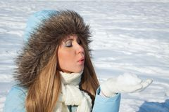 A girl in the park blows snow from her hand. A girl in a blue jacket and white scarf in the park blows snow from her hand Royalty Free Stock Photos