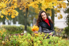 Girl in park colourful autumn. Standing in coat and  vivid foliage around Royalty Free Stock Photo