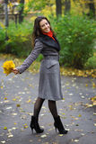 Girl in park colourful autumn. Walking with  vivid bouquet of foliage in hands Royalty Free Stock Photography