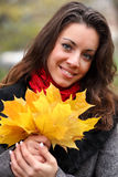 Girl in park colourful autumn. Holding vivid bouquet of foliage in hands Royalty Free Stock Photo