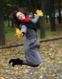 Girl in park colourful autumn. Jumping with vivid bouquet of foliage in hands Stock Photography