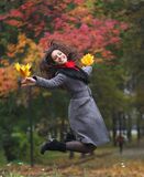 Girl in park colourful autumn. Jumping with vivid bouquet of foliage in hands Stock Photos