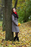 Girl in park colourful autumn. Holding vivid bouquet of foliage in hands Stock Images