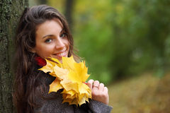 Girl in park colourful autumn. Holding vivid bouquet of foliage in hands Royalty Free Stock Images