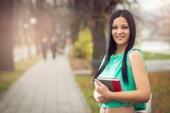 Girl in park holding book Stock Image