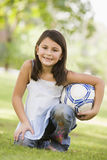 Girl in park holding football Royalty Free Stock Photos