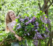 The girl in park with a huge bouquet of a lilac Stock Images