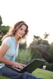 Girl at park with laptop. Nice girl sitting at park with a laptop stock photo