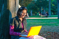 Girl in a park with laptop Stock Images