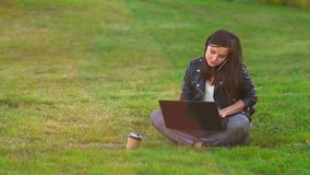A girl in the Park on the lawn working on a laptop, phone rings, answers an incoming call. stock footage