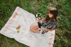 Girl in park looking at bottle of champagne Stock Photos