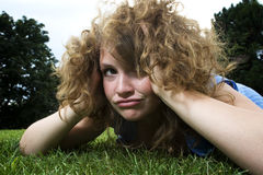 Girl in park making funny face. Laying in the grass Royalty Free Stock Images