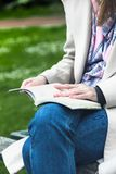 Girl at the park reading a book stock photography