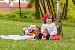 Girl in the park in red riding hood costume Stock Photo