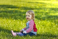 Girl in park sitting on the green grass Royalty Free Stock Photos