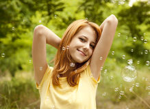Girl in the park under soap bubble rain. Royalty Free Stock Image