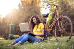 Girl in a park using her laptop Royalty Free Stock Photography