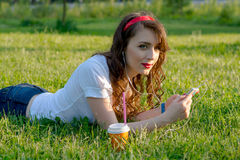 The girl in park wearing headphones with cellphone and a cup of. Coffee resting on the grass Stock Image