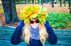 Girl in a park in Wienke of autumn leaves in the park. Close-up. Background Royalty Free Stock Photo