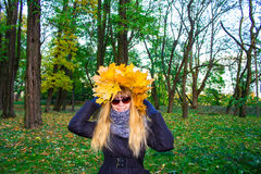 Girl in a park in Wienke of autumn leaves in the park. Close-up. Background Royalty Free Stock Photos