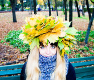 Girl in a park in Wienke of autumn leaves in the park. Close-up. Background Royalty Free Stock Photography